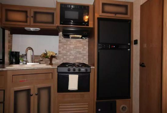 Modern gourmet kitchen has granite-finish counter tops, travertine-finish backsplash, gas range and double-sided porcelain sink with brushed faucet. Microwave, coffeemaker and separate refrigerator and freezer.