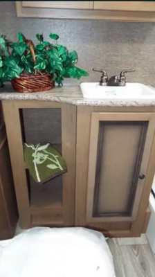 Granite-finish countertops and full vanity with storage in bathroom.