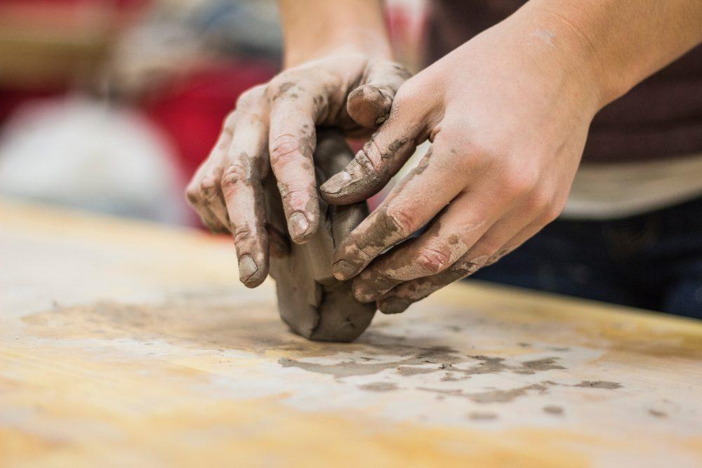 Hands molding clay