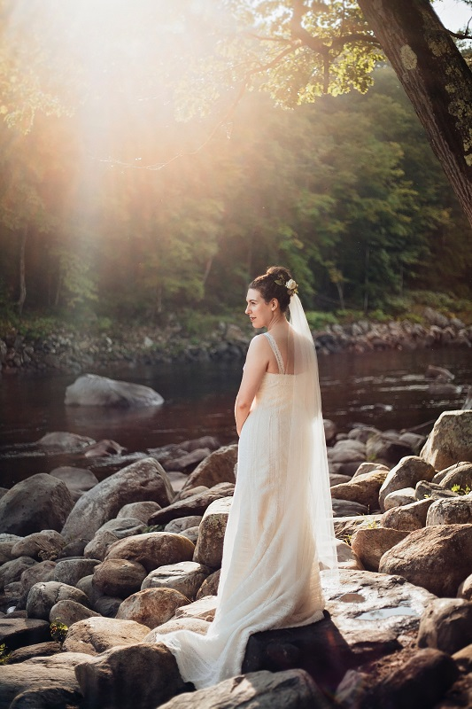 Bride standing in front of river