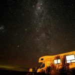 Caravan camped under stars at night