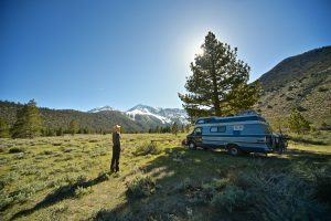 person standing next to a blue RV in nature