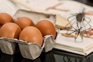 five eggs sitting in a carton next to a whisk