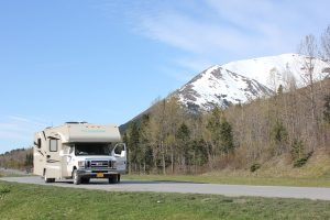white RV driving on a road with a mountain in the background