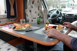 person sitting at a table and eating in an RV