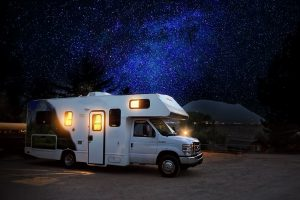 white RV with lights on parked beneath a night sky