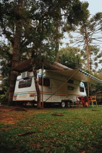 white RV with awning in the woods