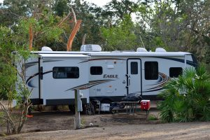 white RV rental delivered and set up at a campground