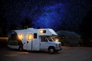 white RV camping under a night sky